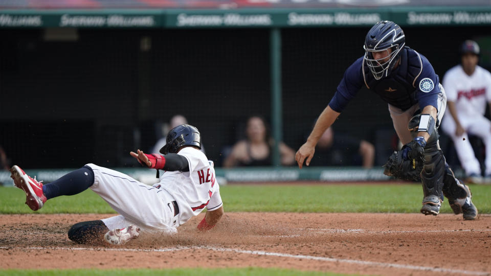 Cleveland Indians' Cesar Hernandez, left, scores as Seattle Mariners catcher Tom Murphy is late on the tag in the 10th inning of a baseball game, Saturday, June 12, 2021, in Cleveland. (AP Photo/Tony Dejak)