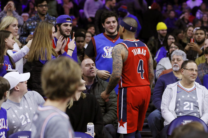Washington Wizards' Isaiah Thomas talks with fans in the stands during the second half of an NBA basketball game against the Philadelphia 76ers, Saturday, Dec. 21, 2019, in Philadelphia. Thomas was ejected from the game after leaving the court. (AP Photo/Matt Slocum)