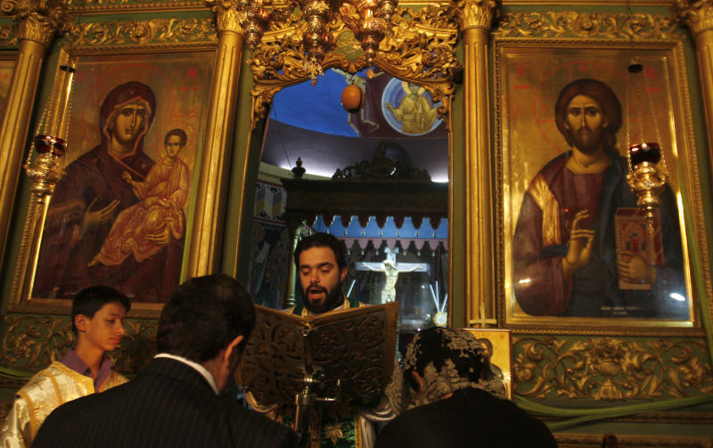 A Christian Orthodox worshipper attends Palm Sunday mass at St. Porphyrius Church, named after Gaza's 5th century bishop, in Gaza City, Sunday, April 8, 2012.  (AP Photo/Hatem Moussa)