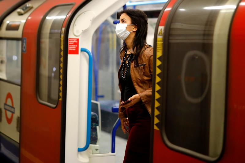 A commuter wears a facemask as she disembarks at a tube station in London on June 5, 2020, as lockdown measures are eased during the novel coronavirus COVID-19 pandemic. - Face coverings will soon be compulsory for people wanting to travel on public transport in England to limit the spread of coronavirus. (Photo by Tolga Akmen / AFP) (Photo by TOLGA AKMEN/AFP via Getty Images)