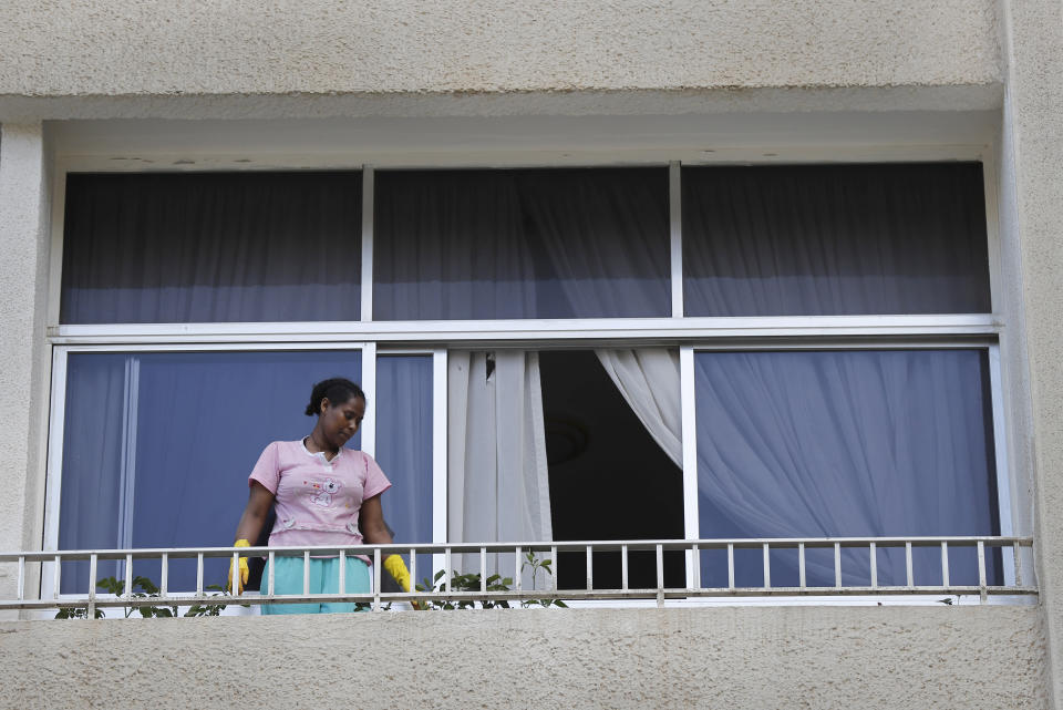 In this Saturday, May 23, 2020 photo, an Ethiopian domestic worker cleans her employer's balcony, in Beirut, Lebanon. Some 250,000 registered migrant laborers in Lebanon — maids, garbage collectors, farm hands and construction workers — are growing more desperate as a crippling economic and financial crisis sets in, coupled with coronavirus restrictions. With no functioning airports and exorbitant costs of repatriation flights, many are trapped, unable to go home. (AP Photo/Hussein Malla)