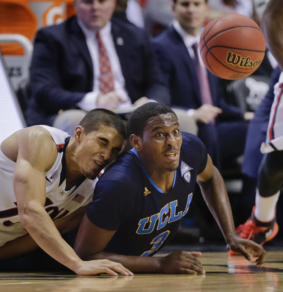 Arizona's Nick Johnson, left, and UCLA's Jordan Adams dive for a loose ball in the second half during the championship game of the NCAA Pac-12 conference college basketball tournament, Saturday, March 15, 2014, in Las Vegas. UCLA won 75-71. (AP Photo/Julie Jacobson)