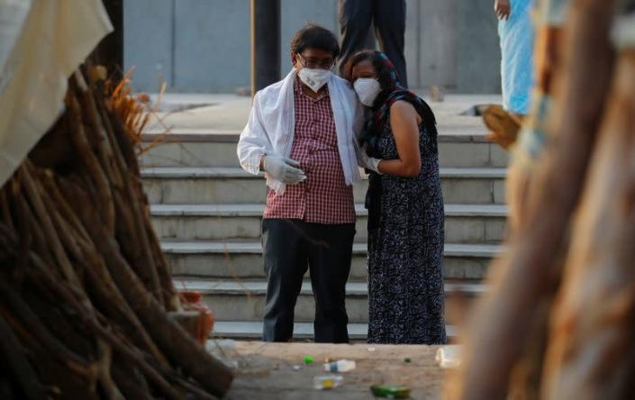 A couple mourns as they stand next to the funeral pyre of a relative who died due to the coronavirus disease (COVID-19), at a crematorium in New Delhi