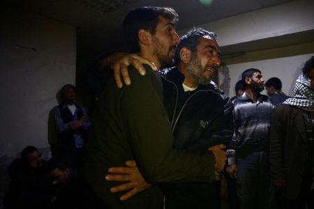 Men mourn the death of their relatives after airstrikes in the rebel held besieged Douma neighbourhood of Damascus