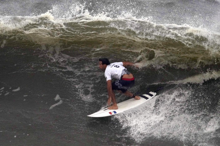 France's Jeremy Flores surfs a wave during the third round of the men's surfing competition at the 2020 Summer Olympics, Monday, July 26, 2021, at Tsurigasaki beach in Ichinomiya, Japan. (AP Photo/Francisco Seco)
