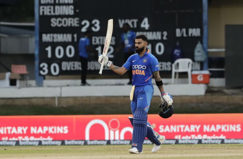 India captain Virat Kohli raises his bats to celebrate reaching a century during the third One-Day International cricket match West Indies in Port of Spain, Trinidad, Wednesday, Aug. 14, 2019. India won by 6 wickets, with 15 balls remaining. (AP Photo/Arnulfo Franco)