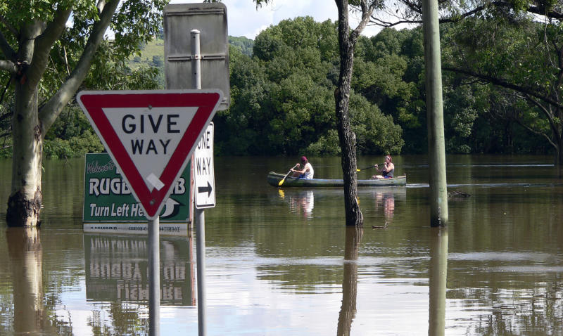 In this photo supplied by NSW State Emergency Service, people use a kayak to make their way through floodwaters caused by torrential rains in Lismore, northern New South Wales, Australia Tuesday, Jan. 29, 2013. Thousands of Australians huddled in shelters Tuesday as torrential rains flooded cities and towns in the northeast. With floodwaters expected to peak in most of the worst-hit areas later Tuesday, officials were rushing to move those in the highest-risk areas to safety. (AP Photo/NSW State Emergency Service, Samantha Cantwell ) NO SALES