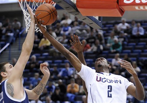 CORRECTS DATELINE TO HARTFORD Connecticut's DeAndre Daniels, right is guarded by New Hampshire's Chris Pelcher during the first half of an NCAA college basketball game in Hartford, Conn., Thursday, Nov. 29, 2012. (AP Photo/Fred Beckham)