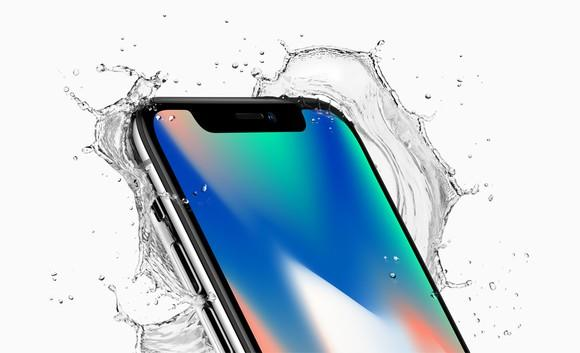 Apple's iPhone X tilted back with water splashing around it.
