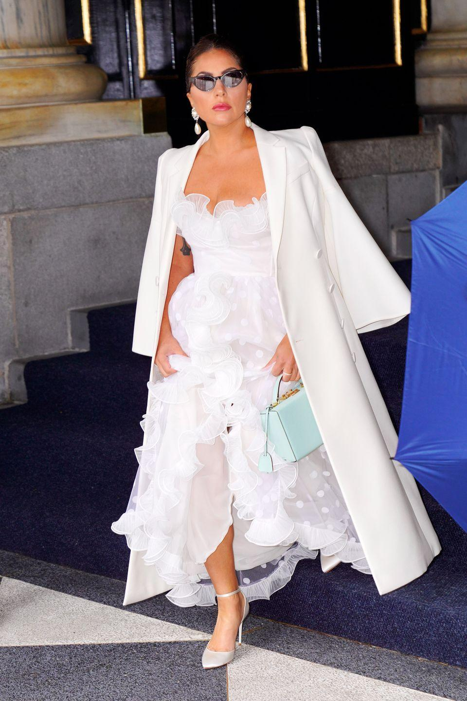 """<p>The singer was photographed leaving a hotel in NYC on June 29 wearing a white tulle Giambattista Valli dress with a scalloped skirt. </p><p>The bridal-esque look was styled with a long white blazer coat, a mint green-coloured bag, white heels and pearl drop earrings.</p><p>While Gaga isn't planning to walk down the aisle to marry her boyfriend Michael Polansky anytime soon, as far as we know, we can't get enough of this chic wedding appropriate number.</p><p><a class=""""link rapid-noclick-resp"""" href=""""https://www.elle.com/uk/fashion/what-to-wear/articles/g31653/modern-spring-wedding-dresses/"""" rel=""""nofollow noopener"""" target=""""_blank"""" data-ylk=""""slk:SHOP MODERN WEDDING DRESSES"""">SHOP MODERN WEDDING DRESSES</a></p>"""