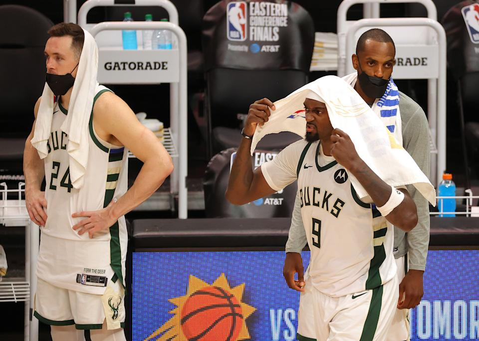 Bobby Portis puts a towel on his head and reacts to the Bucks' loss as his teammates look on dejectedly in the background.