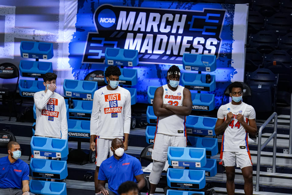 Members of the Florida team, including Jason Jitoboh (33) and Niels Lane (44) watch from the bench in masks in the second half of a first round game against Virginia Tech in the NCAA men's college basketball tournament at Hinkle Fieldhouse in Indianapolis, Friday, March 19, 2021. Restrictions due to the COVID-19 pandemic have limited crowds, reduced interactions and created an abnormal NCAA experience for those involved. It's sacrifices they've all been asked to make by the NCAA to pull off a tournament in the midst of the ongoing pandemic. (AP Photo/Michael Conroy)