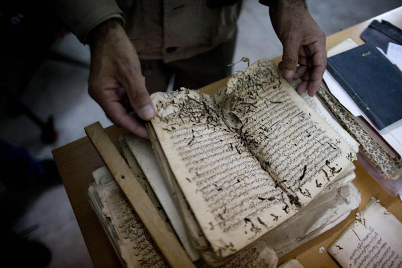 In this photo taken on Monday, Jan. 27, 2014, an employee shows an old manuscript at the al-Aqsa mosque compound library in Jerusalem. The library has a collection of some 4,000 old manuscripts with about a quarter considered in poor condition. Half of the books are already undergoing restoration funded by the Waqf, Jordan's Islamic authority which manages the holy site, and with assistance from UNESCO. (AP Photo/Dusan Vranic)