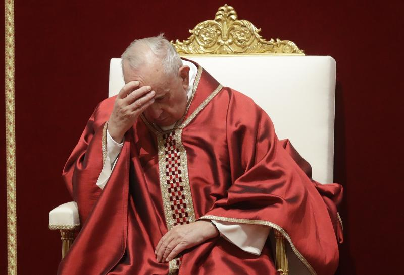 Pope Francis touches his forehead as he celebrates Mass for the Passion of Christ, in St. Peter's Basilica, at the Vatican, Friday, April 19, 2019. Pope Francis began the Good Friday service at the Vatican with the Passion of Christ Mass and hours later will go to the ancient Colosseum in Rome for the traditional Way of the Cross procession. (AP Photo/Alessandra Tarantino)