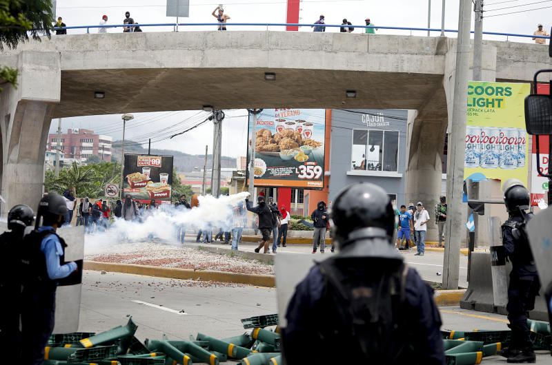 A man throws a tear gas canister back at the police during a protest against the government of Honduras' President Juan Orlando Hernandez in Tegucigalpa, Honduras, Thursday, May 30, 2019. Thousands of doctors and teachers have been marching through the streets of Honduras' capital for the last three weeks, against presidential decrees they say would lead to massive public sector layoffs. (AP Photo/Elmer Martinez)