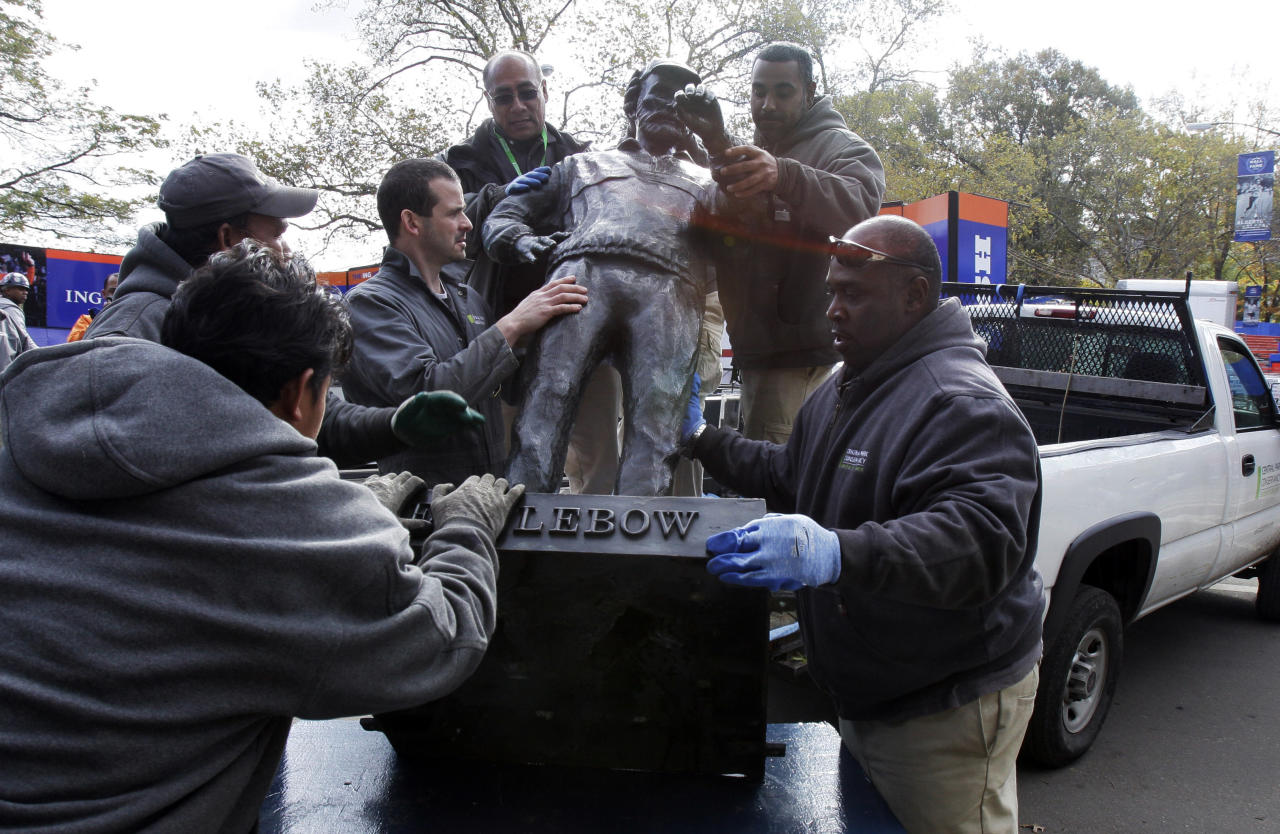 The bronze sculpture of Fred Lebow, the founder of the New York City Marathon, is unloaded by members of the Central Park Conservancy at the marathon finish line, in New York's Central Park, Friday, Nov. 2, 2012. The course for Sunday's New York City Marathon will be the same since there was little damage but getting to the finish line could still be an adventure for runners from outlying areas. Such is life in Sandy's aftermath disrupted trains, planes, buses and ferries, flooded buildings, blocked roads and knocked out power. (AP Photo/Richard Drew)