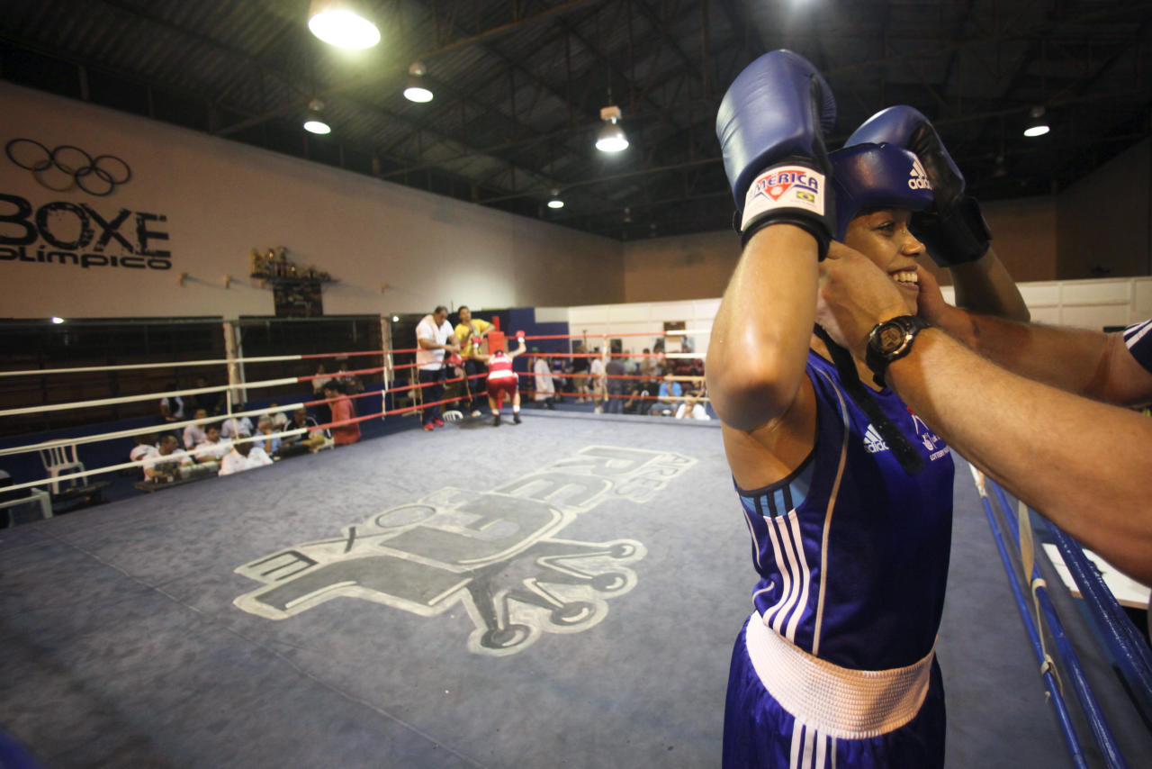 British boxer Natasha Jonas smiles at her coach before a fight with Brazil's Adriana Araujo (L) at the Santo Amaro club in Sao Paulo February 11, 2012. The women's boxing team from Great Britain is in Brazil to train with the Brazilian team between January 29 and February 12. According to the team, this exchange of experience with the South American boxers is part of their strategy for the London Olympics 2012, where women's boxing will be making its Olympic debut. Picture taken February 11, 2012. REUTERS/Fernando Donasci