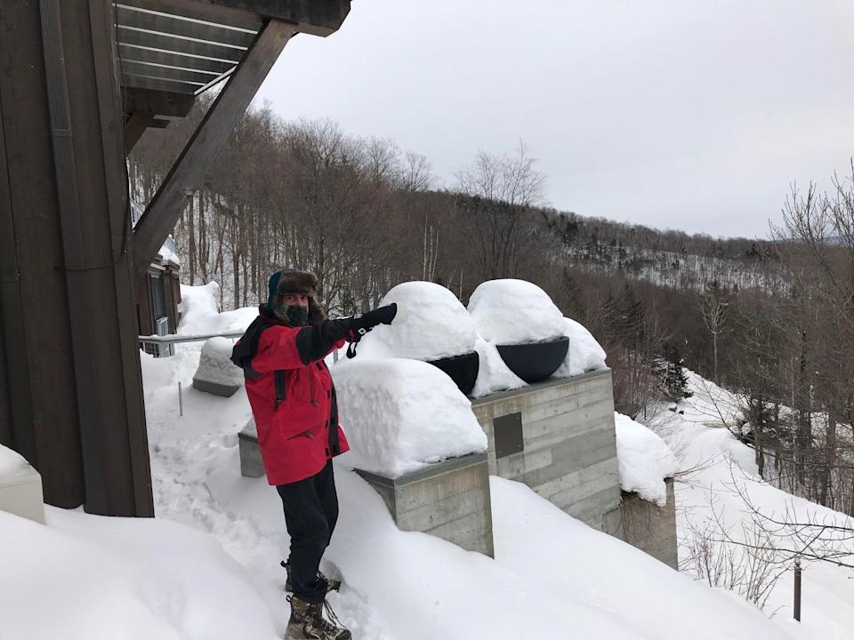 Mike Krancer points to another neighboring house from his perch atop Bull Moose Ridge Road in Stowe, Vt., on Feb. 18, 2021.