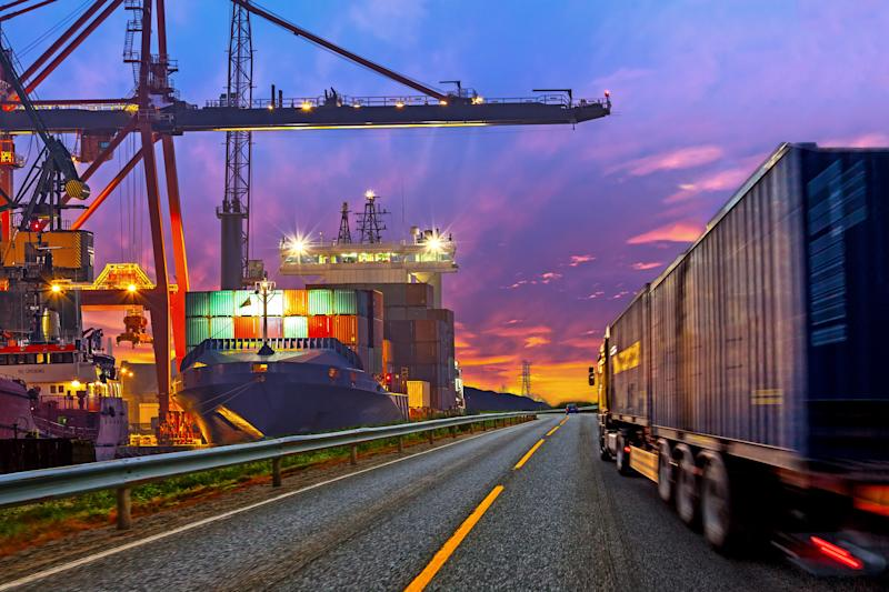 A container ship at a port and a truck on a highway