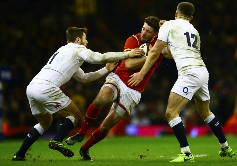 Wales' wing Alex Cuthbert (C) is tackled by England's wing Elliot Daly (L) and England's centre Owen Farrell (R) during the Six Nations international rugby union match between Wales and England on February 11, 2017