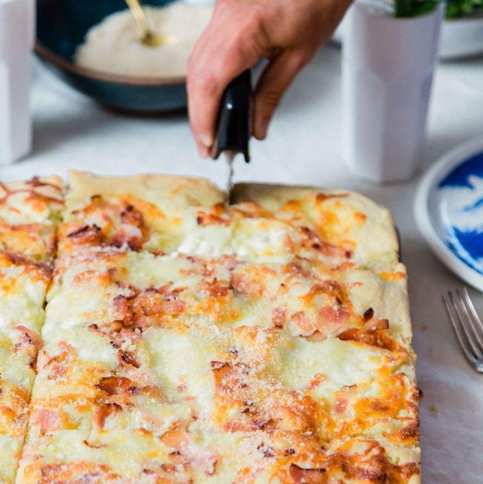 """<p>Why order pizza when you can make your own with light and fluffy focaccia crust, topped with bacon and lots of cheese? Your guests will be begging for more. </p><p><em><a href=""""https://www.womansday.com/food-recipes/a33575711/white-pie-with-bacon-recipe/"""" rel=""""nofollow noopener"""" target=""""_blank"""" data-ylk=""""slk:Get the White Pie With Bacon recipe."""" class=""""link rapid-noclick-resp"""">Get the White Pie With Bacon recipe.</a></em></p>"""