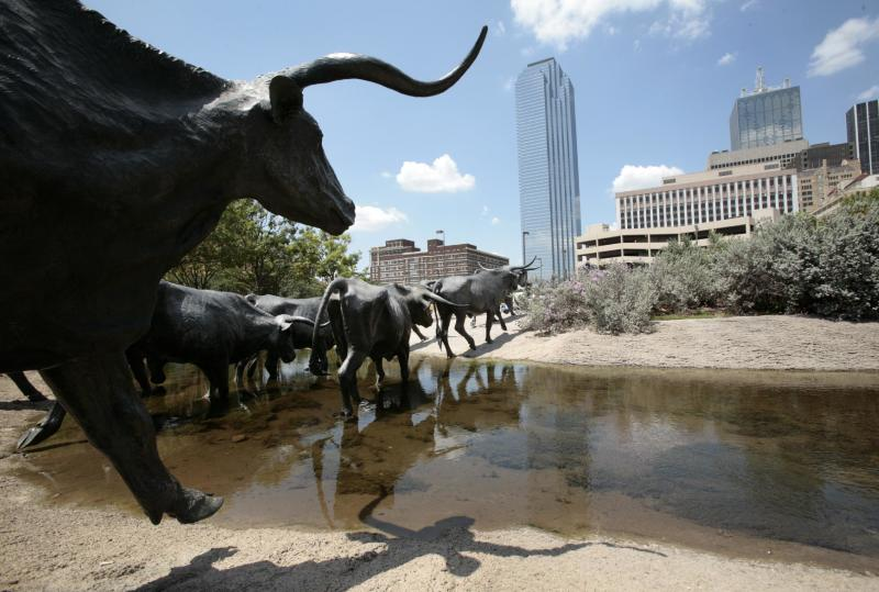 This Aug. 7, 2009 photo shows an outdoor longhorn steer sculpture in downtown Dallas with the Dallas skyline in the background. Dallas is a city that likes to do things big, but that doesn't mean you'll have to sell the ranch to have a good time here. (AP Photo/Tony Gutierrez)