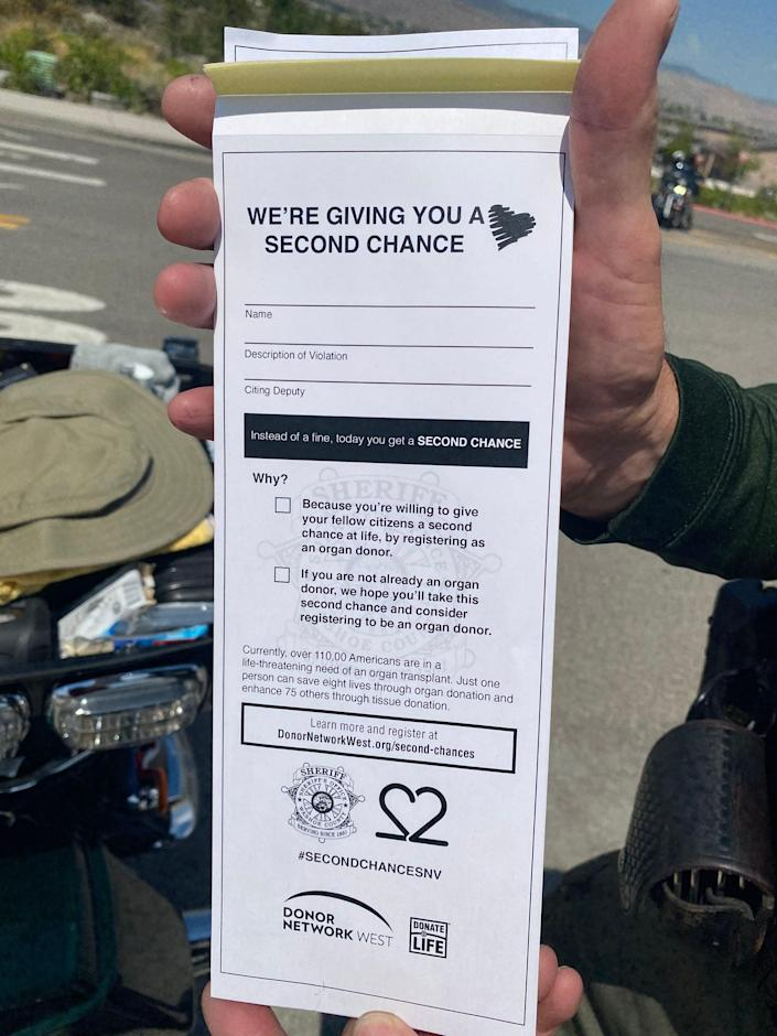 Washoe County Sheriff's Office Deputy Steve Decarli holds a warning ticket with a message about organ donation as part of the 'Second Chance' program this week.