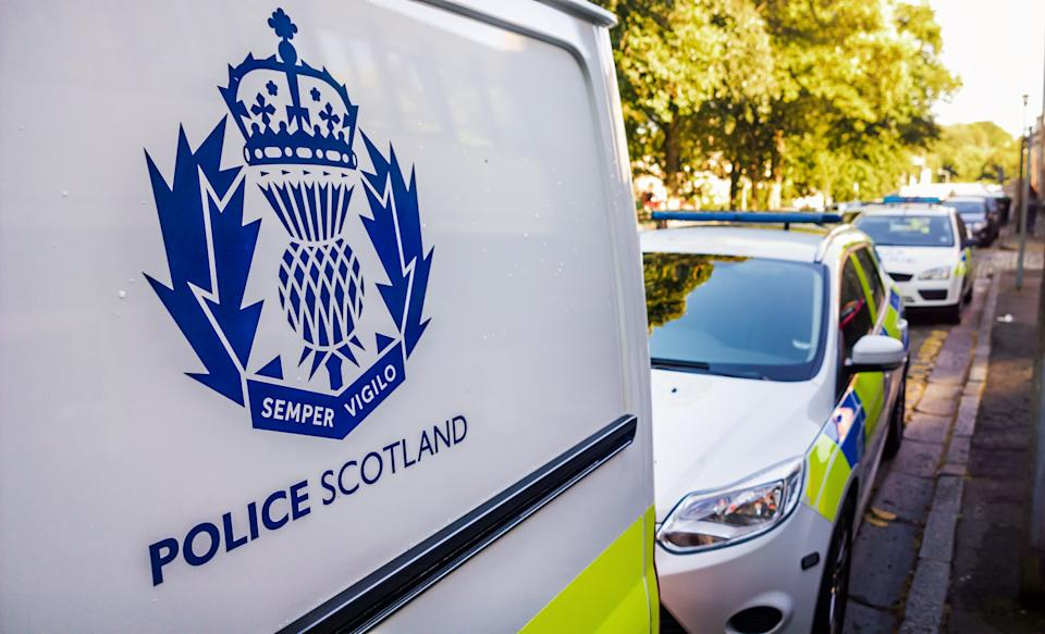 Edinburgh, Scotland, UK - July 16, 2014: The Police Scotland logo on the side of a police van, with other police vehicles in the background. Police Scotland was established in 2013 as an amalgamation of eight regional police forces across the country.