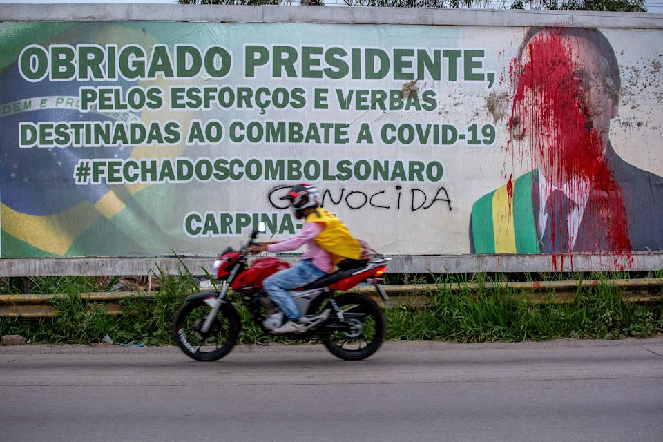 A billboard with the image of  Brazilian President Jair Bolsonaro is seen vandalized with red paint and feces as a protest of his governamental management of the coronavirus (COVID-19) pandemic, in Carpina, Pernambuco state, Brazil, on March 27, 2021. - Since February, Brazil has seen record after record in fatalities and new cases of infection as the country second hardest hit anywhere in the world, after the United States, with more than 307,000 dead from the pandemic. (Photo by Leo Malafaia / AFP) (Photo by LEO MALAFAIA/AFP via Getty Images)