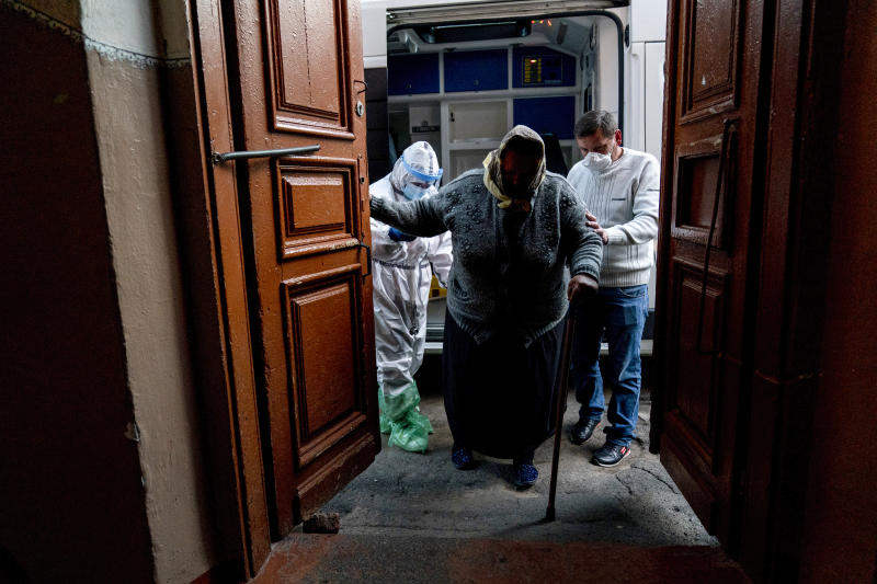 In this photo taken on Saturday, May 9, 2020, ambulance medic Svetlana Padynich, left, helps a patient suspected of having coronavirus to get into the regional hospital of Chernivtsi, Ukraine. Ambulance medics experience shortages of protective gear and many ambulance medics in the city got infected. (AP Photo/Evgeniy Maloletka)