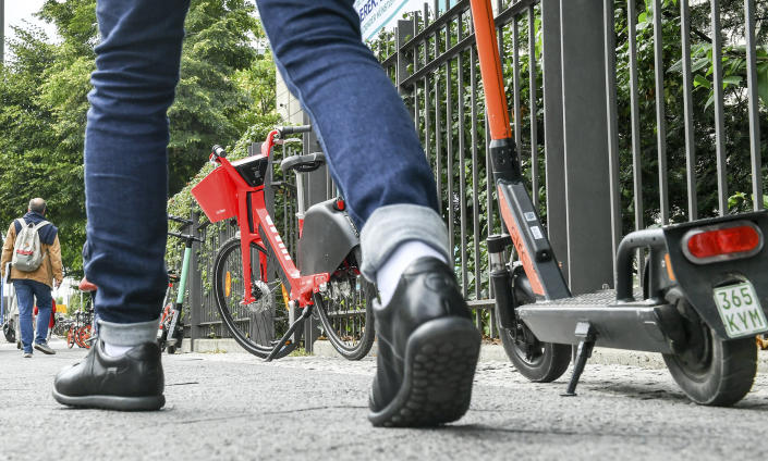 Numerous e-bikes and e-scooters stand on a footpath where pedestrians are on the move. | Jens Kalaene—Jens Kalaene/picture-alliance/dp/AP