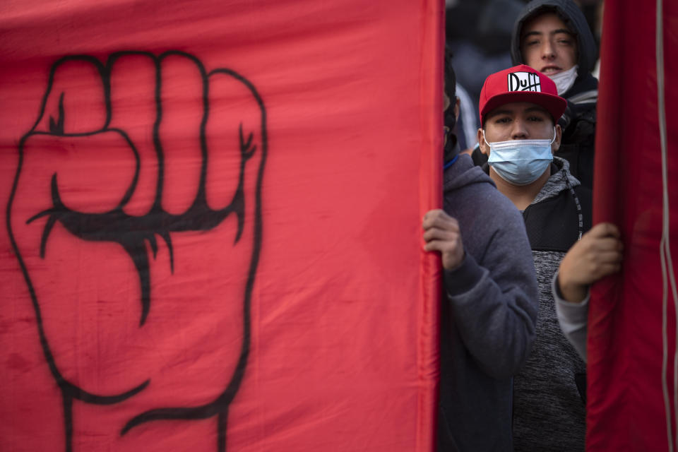 People march to demand better wages and jobs, in Buenos Aires, Argentina, Friday, June 18, 2021. In the midst of a second wave of the new coronavirus, healthcare workers and social organizations marched due to high inflation and increasing poverty. (AP Photo/Victor R. Caivano)