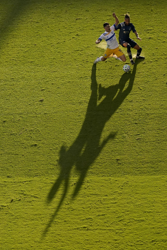 San Jose Earthquakes forward Cristian Espinoza, left, and Sporting Kansas City defender Amadou Dia battle for the ball during the first half of an MLS soccer match Sunday, Nov. 22, 2020, in Kansas City, Kan. (AP Photo/Charlie Riedel)