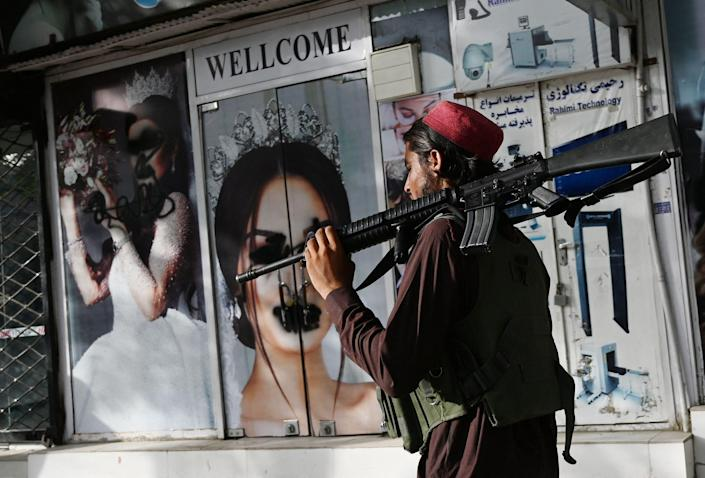 A Taliban fighter walks past a beauty saloon with images of women defaced using spray paint in Shar-e-Naw in Kabul, Afghanistan on August 18, 2021.