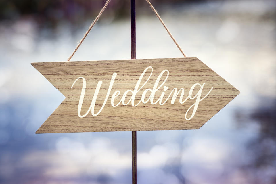 Wedding ceremony wooden arrow location sign with lake reflection background