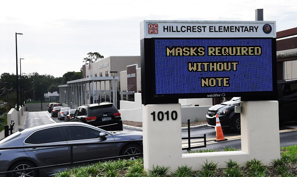 Parents drop their kids off at Hillcrest Elementary school in Orlando with a sign at the entrance advising for the requirement of face masks for students unless the parents opt out of the mandate by writing a note to school officials. (Paul Hennessy/SOPA Images/LightRocket via Getty Images)