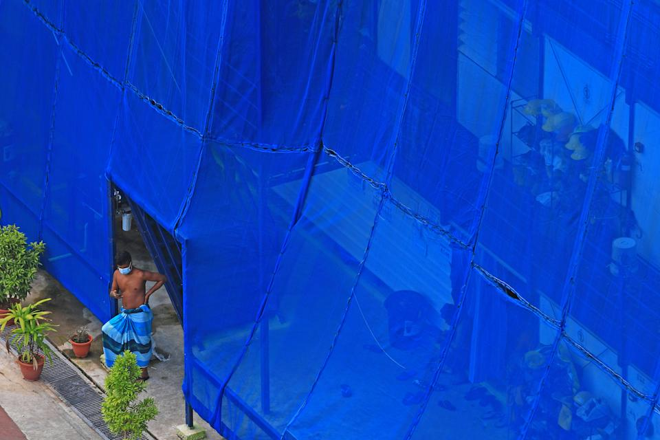 SINGAPORE - MAY 28:  A migrant worker stands outside his makeshift dormitory room, fitted with exterior netting, at a stalled construction site on May 28, 2020 in Singapore. Singapore is set to ease the partial lockdown measures against the coronavirus (COVID-19) pandemic after 1 June in three phases to resume activities safely after it sees a decline in the new infection cases within the community. Building contractors will be allowed to gradually resume operations from June 2, with  safe distancing measures in place, such as implementing contract tracing at worksites and avoiding cross deployment of workers.  (Photo by Suhaimi Abdullah/Getty Images)