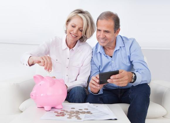 Older couple with coins spread out on a table. The woman is putting some coins into a piggy bank while the man looks on