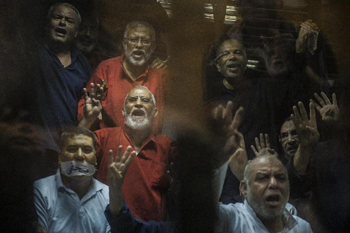 Egyptian Muslim Brotherhood leader Mohamed Badie (centre) gestures from behind the defendant's cage in Cairo on May 16, 2015 (AFP Photo/Khaled Desouki)