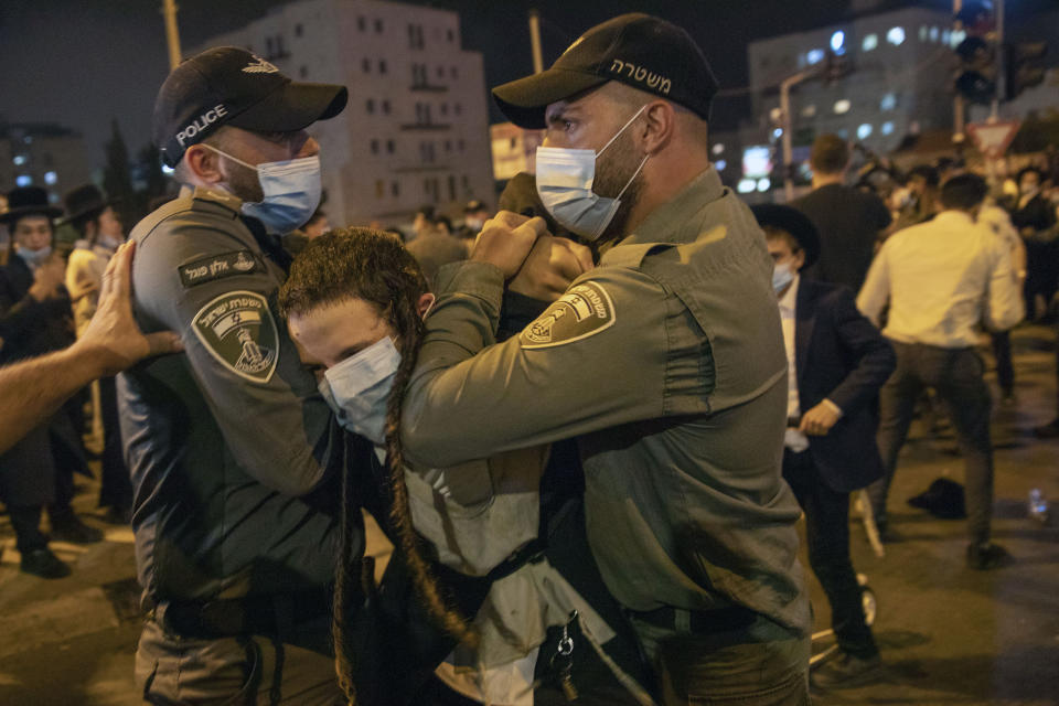 Israeli border police officers arrest an Ultra-Orthodox Jewish man during a protest against lockdown that has been placed in their neighborhood due to a coronavirus outbreak, in Jerusalem, Monday, July 13, 2020. As Israel grapples with a spike in coronavirus cases, it has begun to impose restrictions on selected towns and neighborhoods with high infection rates. Many of these areas are ultra-Orthodox, and residents say they are being unfairly singled out. (AP Photo/Oded Balilty)