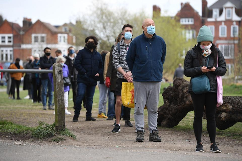 <p>People stand in line for coronavirus surge testing on Clapham Common, south London</p> (PA)