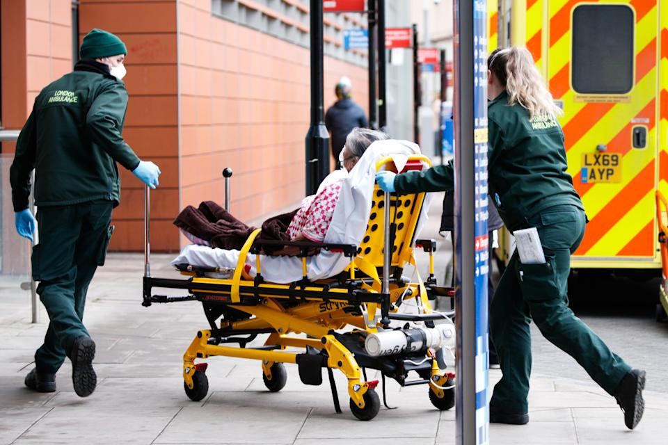 Paramedics wheel a patient wearing an oxygen mask into the emergency department of the Royal London Hospital in London, England, on January 26, 2021. Data from the UK's official statistics bodies revealed today that, based on death certificates, up to January 15 this year nearly 104,000 people have died with coronavirus since the pandemic began. Government figures, which are based on deaths within 28 days of a positive covid-19 test, remain slightly lower, yesterday standing at 98,531. (Photo by David Cliff/NurPhoto via Getty Images)