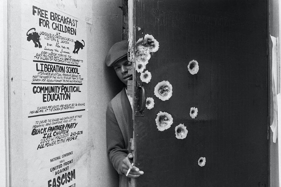 An unidentified member of the Black Panthers peeks around a bullet-pocked door that police blasted with gunfire during a predawn raid in Chicago.