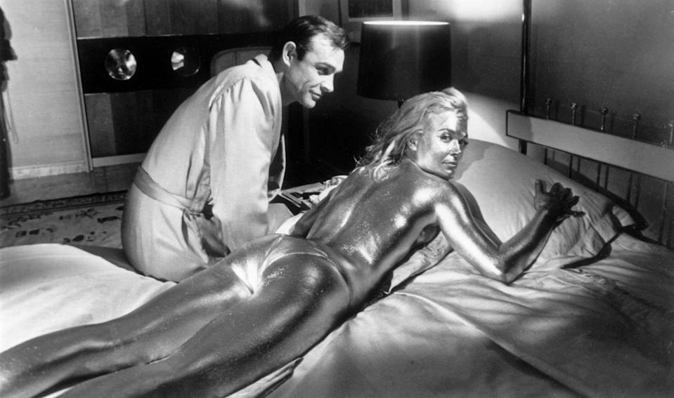 <p>Sean Connery sitting beside his co-star English actress, Shirley Eaton, covered in gold during the filming of a scene from Goldfinger.</p>