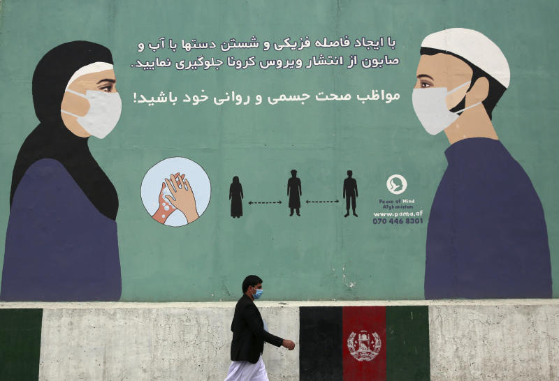 FILE-In this May 11, 2020, photo, a man wearing a protective face mask to help curb the spread of the coronavirus, walks past a painted wall of Ministry of Public Health, which gives instructions on measures to help curb the spread of the coronavirus in Kabul, Afghanistan. A prominent international aid organization warned Tuesday, June 2, 2020 that Afghanistan is on the brink of a humanitarian disaster because the government is unable to test at least 80% of possible coronavirus cases. (AP Photo/Rahmat Gul, File)