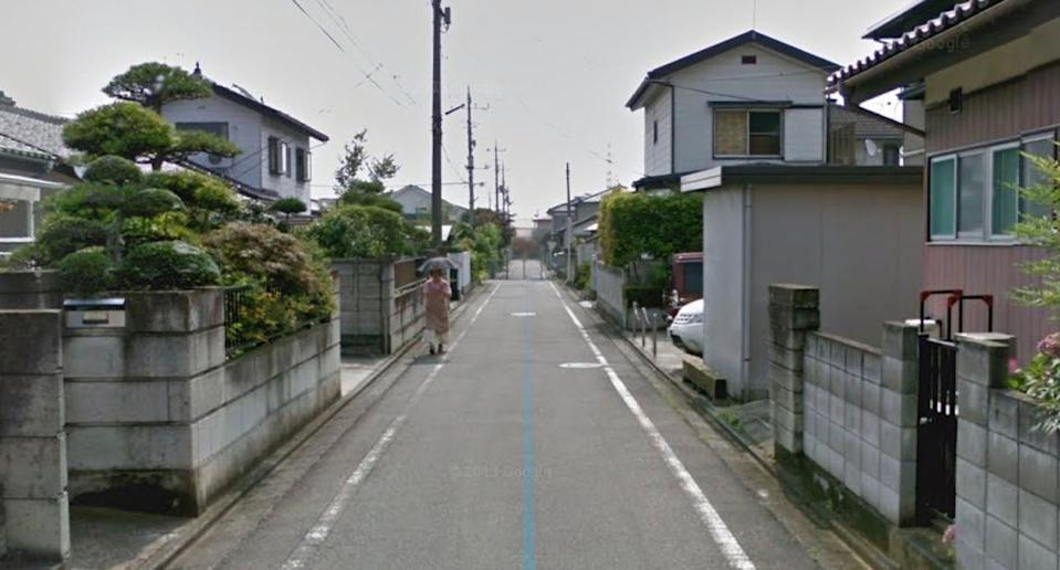 Pictured is a woman walking on the street in a Google Earth image.