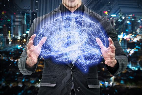 Man in a suit holding a wireframe brain connected to an electronic circuit graphic with a bokeh city background.