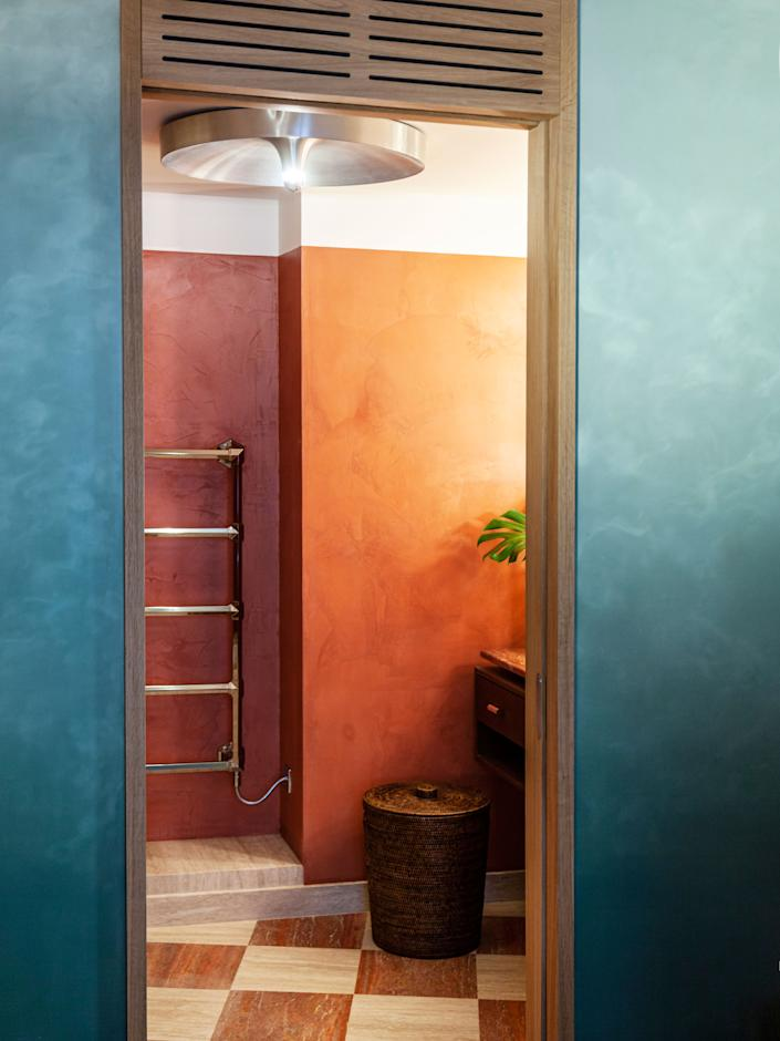 """<div class=""""caption""""> In the master bathroom, a <a href=""""https://www.pamono.com/french-metal-sconce-by-charlotte-perriand-1970s-1"""" rel=""""nofollow noopener"""" target=""""_blank"""" data-ylk=""""slk:Charlotte Perriand ceiling fixture"""" class=""""link rapid-noclick-resp"""">Charlotte Perriand ceiling fixture</a> combines with a <a href=""""https://www.baolgichic.com/en/"""" rel=""""nofollow noopener"""" target=""""_blank"""" data-ylk=""""slk:Baolgi Chic rattan basket"""" class=""""link rapid-noclick-resp"""">Baolgi Chic rattan basket</a>. </div>"""