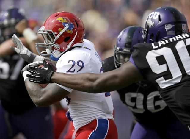 Kansas running back James Sims (29) breaks through the TCU defensive tackle Chucky Hunter (96) and Terrell Lathan (90) for extra yardage on a running play in the first half of an NCAA college football game, Saturday, Oct. 12, 2013, in Fort Worth, Texas. (AP Photo/Tony Gutierrez)