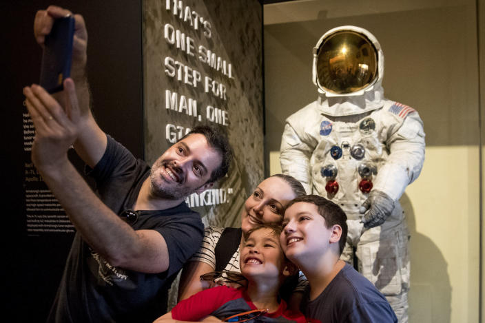 Rafiel Santos and Silvia Freddo, and their two children Jose Eduardo, 11, right, and Gustavo, 6, bottom, of Santa Catarina, Brazil, take a selfie as some of the first visitors to view Neil Armstrong's Apollo 11 spacesuit after it is unveiled at the Smithsonian's National Air and Space Museum on the National Mall in Washington, Tuesday, July 16, 2019. (AP Photo/Andrew Harnik)